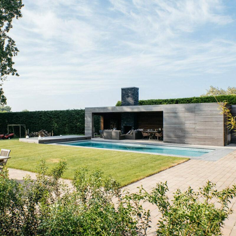 bijgebouw of poolhouse in een tuin met een zwembad