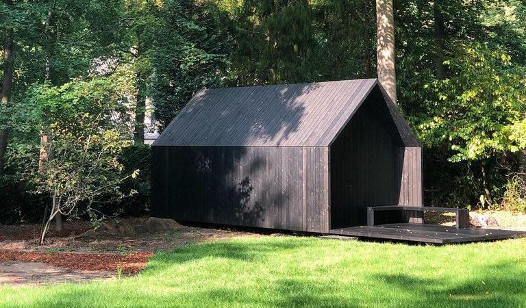 bijgebouw in het zwart in een tuin