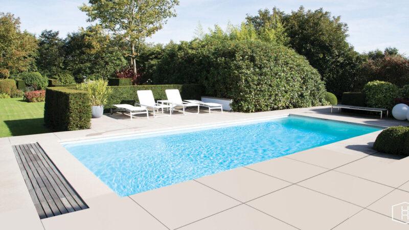 zwembad met terras en ligbedden